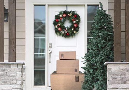 front door with christmas wreath and packages